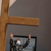 Woman in mask stands in front of cross, with arms up