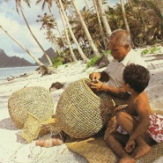 Photo on a beach in Samoa of a fisherman and boy with a basket