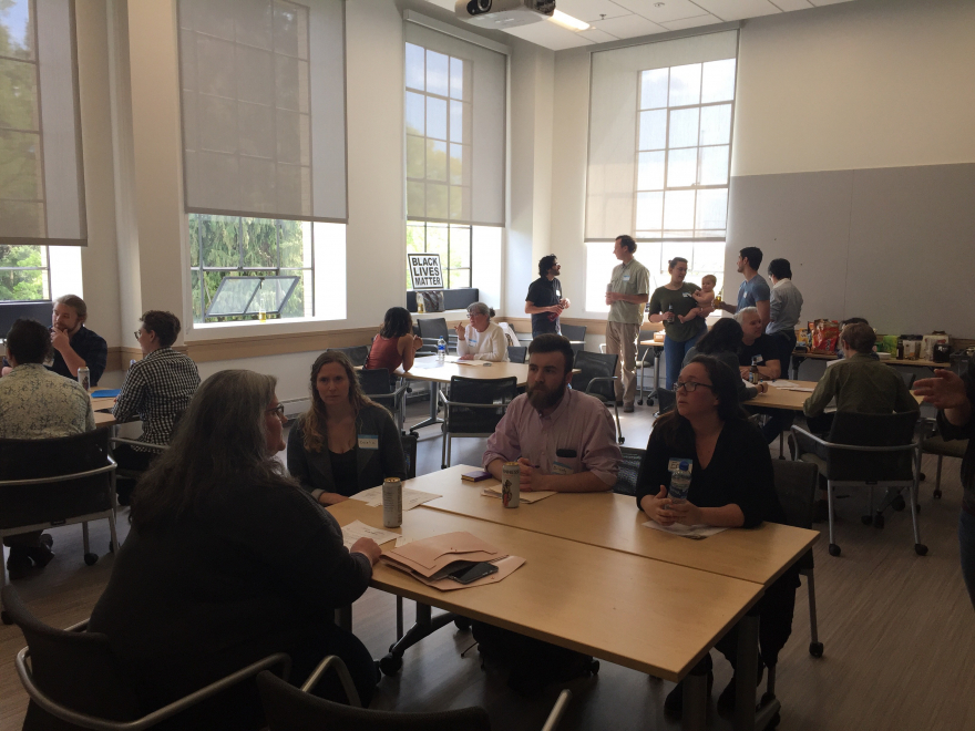 Photo of Denny Hall 313, on April 26th featuring tables with students and consultants in discussion