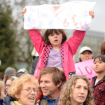 Brian Wahlberg gives daughter Luciena a good view of the proceedings as the crowd sings at Cal Anderson Park in Seattle.