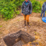Photo of Hollis Miller in front of an excavated test pit