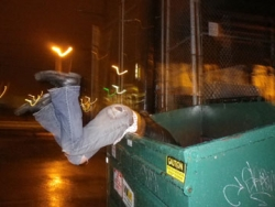 A man hanging over the side of a dumpster