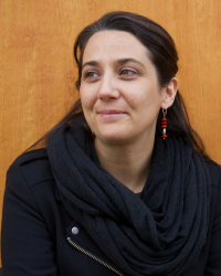 Portrait of Prof. Rabanes, a woman with medium-light skin, black hair, wearing a black jacket and red earrings. She is smiling, looking to the side, armed crossed, leaning against a wall.