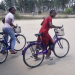Two Mozambican community activists on bikes heading to do home visits to people in the community living with HIV.