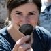 Community volunteer Katelyn Sikes holds up a flake from a groudstone adze dating to roughly 3400 years ago from the Mitks'qaaq Angayuk Site on Kodiak Island, Alaska