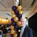 John Cady at the Staff Awards, standing in front of gold and purple balloons